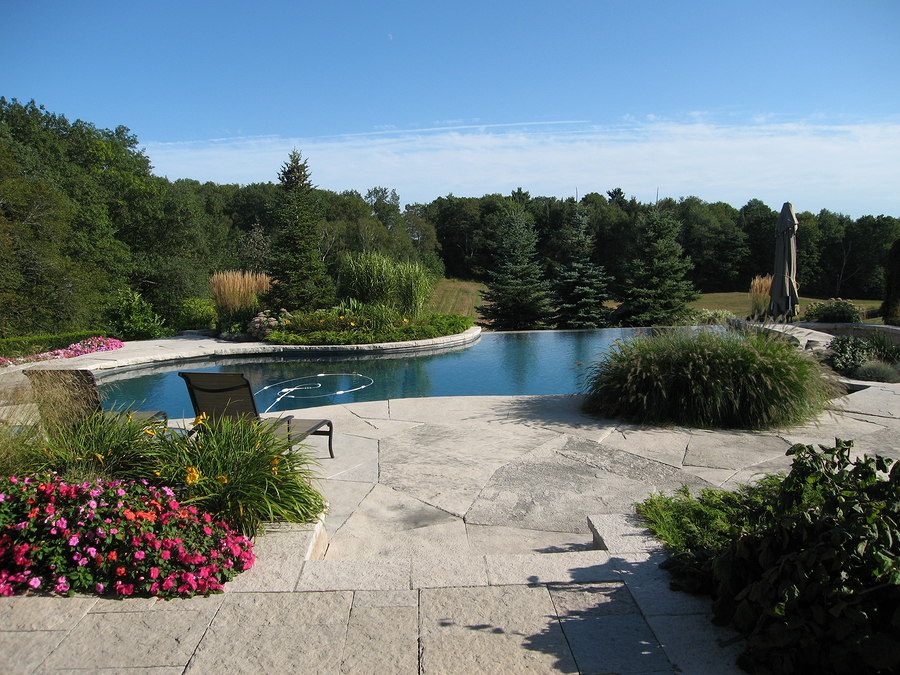 a natural stone pool can enhance the versatility of your backyard landscape